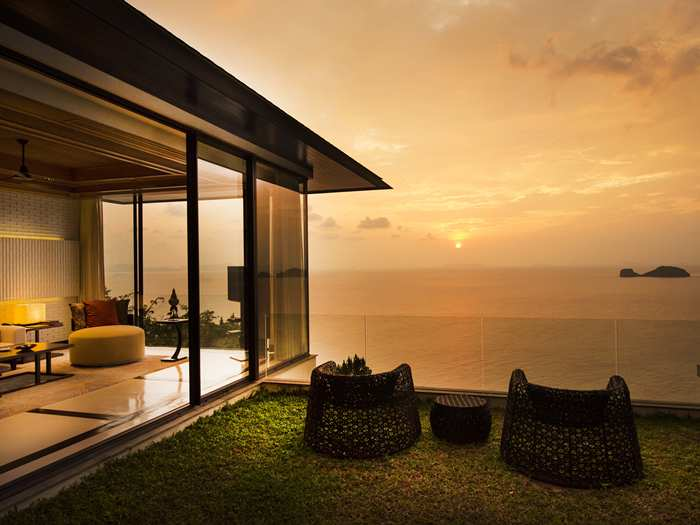 The upper floor entrance opens onto an emerald lawn replete with seating area from which to view the sprawling seascape below.